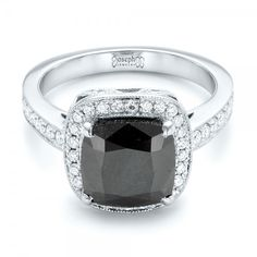 #102814 This stunning engagement ring features a cushion shaped black diamond, prong set in white gold, and surrounded by a halo of round white diamonds. It...