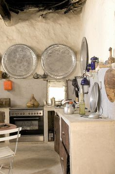 Very rustic kitchen, with super large round tin platters hanging on wall above kitchen workspace, very boho via: Moon to Moon: Creating a Bohemian kitchen...