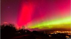 The Aurora Borealis seen in pink and orange over a British landscape