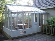 A custom 10 x 14 Garden Deluxe greenhouse with one end attached to the house. Customized with taller glass walls to allow for a door in the side.