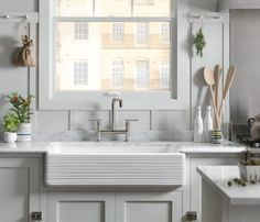 Herbs and oils in a bright kitchen, farmhouse sink