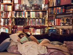Girl lays on sofa reading in front of epic bookshelf