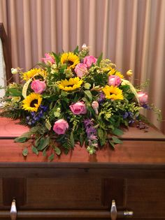 Pink roses and sunflowers in a casket spray.