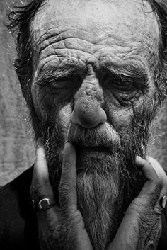 First of all, I love this picture. The expression of the subject evokes very strong emotions even though it is in B&W. The photo also uses a shallow depth of field by placing the emphasis on the sharpness of the man's wrinkles and his hands while blurring the hard lines of the back ground.