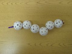 Fine motor task.  Threading wiffle golf balls onto a pipe cleaner.