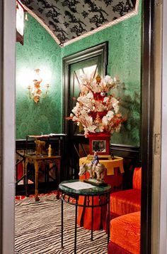this room combines dragon motifs, fretwork, malachite wallpaper and antiquities from the Ming and Tang dynasties. Malachite Fornasetti wallpaper by Cole & Son