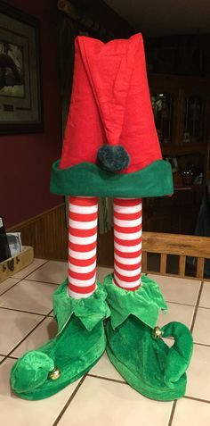 Elf centerpiece so easy to make! Pool noodle cut in half, elf socks, elf shoes, elf hat placed on top of legs - all for under $10