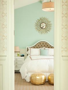 gorgeous blue walls paint color, blue gold tufted silk headboard, gold starburst mirror, gold metallic Moroccan poufs, linen drum pendant, gold circles rug, turquoise blue pillow and white bedding with red trim.