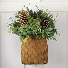 """Door Basket with Greenery evergreens include noble fir, western red cedar and incense cedar accented with silvery blue-berried Oregon juniper, red twig dogwood and natural pinecones. 17"""" wide, 22"""" high."""