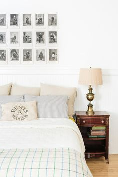 """We decided to let the original wainscoting serve as our headboard in the bedroom. The """"handsome men"""" above the bed were an Etsy purchase and the brass lamp was my great grandfather's. The hardware on the nightstand is from Anthropologie and the flour sack was an estate sale find, lovingly made into a pillow by my sister."""