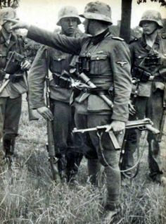 Waffen SS during the fighting in France, summer 1940. Platoon leader gives instructions. Note the young rifleman standing at attention while listening -- typical reaction inculcated into every Waffen SS man by fierce training. The platoon leader is armed with an MP40 SMG.