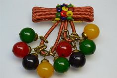 A colorful, charming vintage Bakelite brooch with cherry, blue, green, and butterscotch beads. #jewelry #vintage #brooch