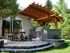 Contemporary Outdoor Kitchen Pergola - The design of this backyard in New Jersey was a catalyst to create a very dynamic outdoor kitchen pergola. This contemporary home featured several very prominent arched windows. Working with these architectural details, the homeowner's landscape designer created a circular patio to encompass a new outdoor dining and kitchen area.