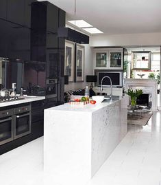 Black cabinetry adds drama in the high-spec kitchen. Pendant light from Fabbian. Tapware from Reece. Marble on island bench from Amalgamated Marble. Floor tiles from Artistic Tile Design. Miele appliances.
