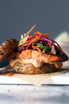This yummy sandwich features an Asian marinated Alaska salmon fillet with a tasty sesame slaw! It& a quick and delicious meal that can be made in a little over 30 minutes! Recipe includes grain and gluten-free alternatives! Salmon Recipes, Fish Recipes, Seafood Recipes, Asian Recipes, Cooking Recipes, Healthy Recipes, Salmon Sandwich, Salmon Burgers, Tostadas
