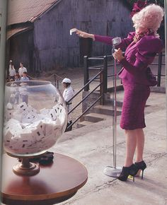 From The Hunger Games Official Illustrated Movie Companion: Woahs. Effie's looking a tad prego in this one! haha