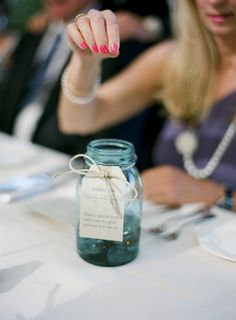 The bride & groom placed a piece of sea glass at each place setting and then passed this jar around with the note to make a wish for the couple ...  Love this idea!  Photo by tanjalippertphoto...
