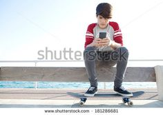 Attractive and thoughtful teenager boy relaxing with a skateboard and sitting down on a bench by the sea, holding and using a smartphone for networking during a sunny day, outdoors. - stock photo