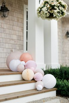 Idée déco pastel pour un baptême ou un mariage. Les lampions et boules en papier sont simplement posés sur les deux côtés d'un escalier.
