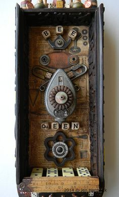 Recycled art assemblage using wood box, manual pages, acrylic paint, game pieces, chalk line tool, safety pins, salvaged metal, steam basket pieces by redhardwick