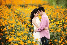 Against a backdrop of orange and yellow flowers // Andreas and Monicha's Engagement Shoot in Bali