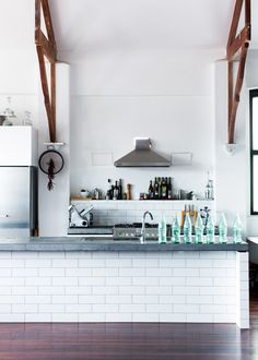 White subway tiles, wooden brace beams on the ceiling and a stone (slate?) benchtop.