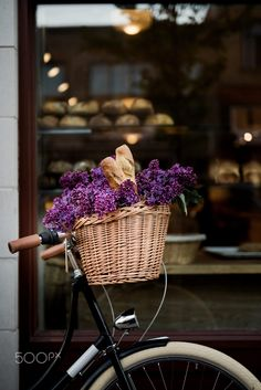 Bicycle with a basket with fresh bread and flowers against a bakery
