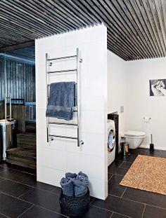 Järkevää ja kekseliästä tilankäyttöä. Sauna jätettiin remontissa vanhalle paikalleen, mutta muoto ja avautumissuunta vaihdettiin. Remontin suunnittelija halusi hyödyntää lauteiden alaosan. Lauteiden viereiseen seinään upotettiin pyykinpesu- ja kuivauskoneet. Näin kylpyhuoneen yhteyteen muodostui kodinhoitotila. Koneet lähes häviävät valkoiseen seinäpintaan, ja tila on helppo pitää siistinä. | Kaupunkilainen savusauna | Koti ja keittiö Bathroom, Home And Living, Sauna, Dream Rooms, Furniture, Home, Laundry Room, Home Decor, Room