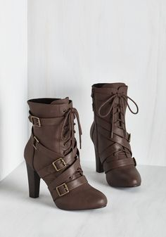 Zip into these brown boots and get ready to be in the spotlight! Boasting a bold combination of gold-buckled straps, laces, and smooth vegan faux leather, these edgy heels set scene for a trove of fantastic ensembles.