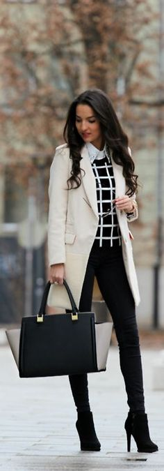 White coat, black skinny pants, b/w sweater, high heel booties, and modern color block purse.
