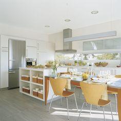 Cocina de estilo contemporáneo con muebles blancos, electrodomésticos de acero inoxidable y sillas de madera en el office