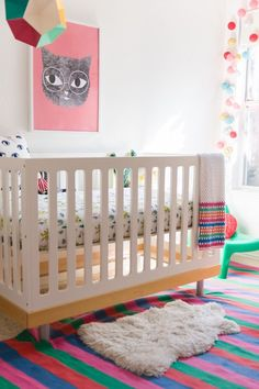 We love the eclectic, colorful design of this  Bohemian-themed nursery. Playful wall art and eye-catching accent pieces make this room a bright, cheerful, and stimulating space for a baby girl to grow in.