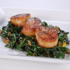 Michael Symon's Seared Scallops These lush scallops take on the flavors of the dish's surrounding ingredients like golden raisins, white wine, and pistachios.