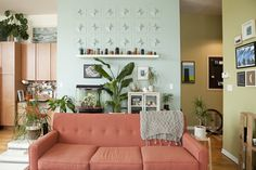 Muted aqua wall + muted salmon sofa + big green leafy plant + minimalist floating shelf with tiny guys