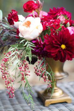 red pink and yellow flowers, roses, dahlias carnations and berries