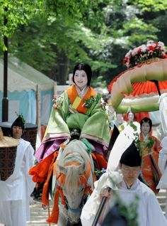 Hollyhock festival. A woman wearing junihitoe and has a hollyhock leaf pinned to her robes.