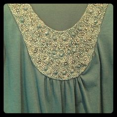 Beaded bib blouse Scoop neck, three quarter sleeve blouse has an elastic hem and elastic at the sleeve ends. There is one spot where the threads in the detailing are loose, but it's easily hidden! The detail in this blouse means you don't even need a necklace! Normal pilling. Agenda Tops Blouses