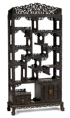 ASIAN ARTS - SALE 1485 - LOT 114 - FREEMAN'S AUCTIONEERS. Large Chinese carved hongmu display shelf  19th century  Shaped apron over alternating shelves, mounted with fret carved edges over two cupboards, raised on carved feet.  H: 71 L: 38 D: 14 1/2 inches   Estimate $2,000-3,000