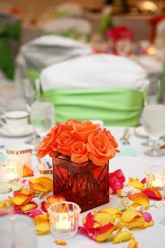 bright orange roses in orange glass cube with multi color petals