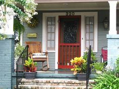 """A neat and tidy front porch with a humble rocker, a red screen door and an abundance of leafy and flowering plants conveys a """"lived in"""" but """"well taken care of"""" feeling. Photo by ©Lisa Heindel. Posted via diynetwork.com"""