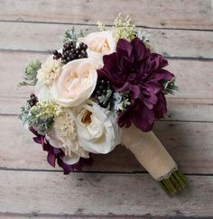 This rustic wedding bouquet is arranged with blush and ivory garden roses and dahlias, with larger pops of plum dahlias, accented with soft green dusty miller and deep purple berries. This wedding bouquet is wrapped in ivory satin and lace, but can be customized to coordinate with your wedding colors. This bouquet measures 10 inches wide and 12 inches tall. Smaller bridesmaids bouquets or toss bouquets can be made to order. ***Current production time is between 6-8 weeks.*** Please contact…