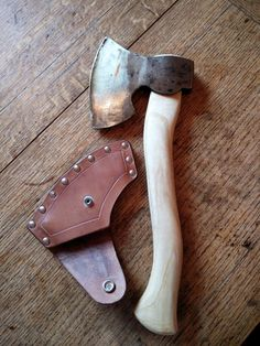 New, hand forged side axe, in the form of an English 'Coach Maker's' axe. Haft hand carved in English Ash, with sheath in 'Veg tanned leather. Blacksmith: Josh Burrell, haft and sheath: Hedgerow Turning.