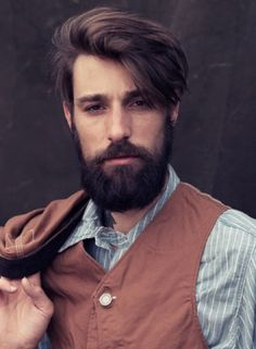 Longish undercut hair with full (but neat) beard and moustache.