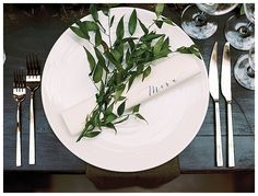 Place setting of white china with modern flatware, delicate greenery and a menu scroll with graceful calligraphy. Image by Nina & Wes Photography.
