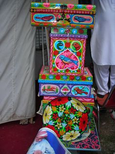 Truck art artist's paintwork on tin items at Lok Virsa Mela, Islamabad, Pakistan. Lok Virsa Mela is a folk heritage annual event in Spring season in Islamabad, where craftsmen and craftswomen from all provinces of Pakistan gather and display their work and sell their handcrafted artwork of all kinds. There is an 'Artisans at work' segment where artisans show how they produce an artwork.  Photography: Zehra Naqavi (Architect/artist).  April 11, 2012  All photographs are watermarked.