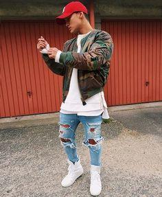 Um look urbano com uma calça rasgada, boné, tenis branco cano alto, uma camisa branca alongada e uma terceira peça que é uma jaqueta militar pra compor com mais estilo essa roupa massa. #MaleFashoinTips