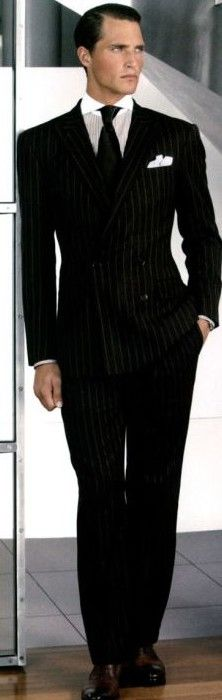 Black striped, double-breasted suit with a black tie over a white spread collar and white pocket square. Homage to the gangster era; the days when the difference between a man and a Man of Honor was quite literally life and death. Designed by Ralph Lauren. Luciano would have been proud.