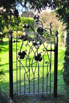 une petite porte de jardin en fer forgé à motifs floraux                                                                                                                                                      Plus