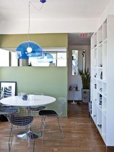 Comedor integrado al living de un departamento de pocos metros cuadrados. Lámpara Fly con pantalla azul, de Kartell, y pared verde con espejo longitudinal sin marco.