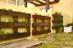 Vertical pallets used as planters on an outdoor wall | 1001 Pallets